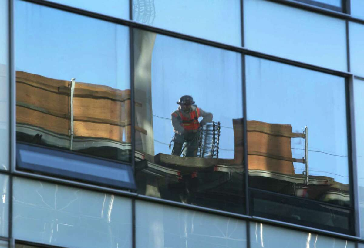 A worker on a residential building project at 10th and Mission streets is reflected in another under-construction building across the street in San Francisco on Tuesday.