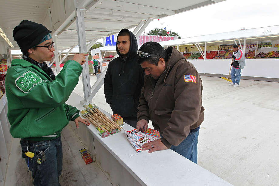 Timothy Esquivel, left, helps Mario Ramirez, right, and his son, Mark Ramirez, as they shop at the Alamo Fireworks Megamarket located at 2880 Pue Road out in West Bexar County, Tuesday, Dec. 30, 2014. The megamarket is made up of six fireworks stands surrounding a concrete slab. Customers are able to shop at the stands that are separated by different types of fireworks. Photo: JERRY LARA, Staff / San Antonio Express-News / © 2014 San Antonio Express-News