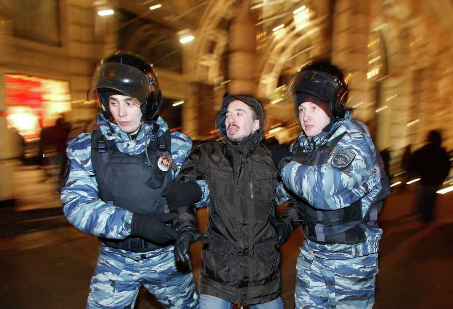 Police officers detain a protester during an unsanctioned protest in Moscow, Russia, Tuesday, Dec. 30, 2014. The unsanctioned protest came hours after Alexei Navalny was found guilty of fraud and given a suspended sentence. Navalny, who has been under house arrest since February, is accused of breaking the terms of his house arrest to attend the rally and was detained by police as he approached the site of the protest. (AP Photo/Denis Tyrin) Photo: Denis Tyrin, STR / AP