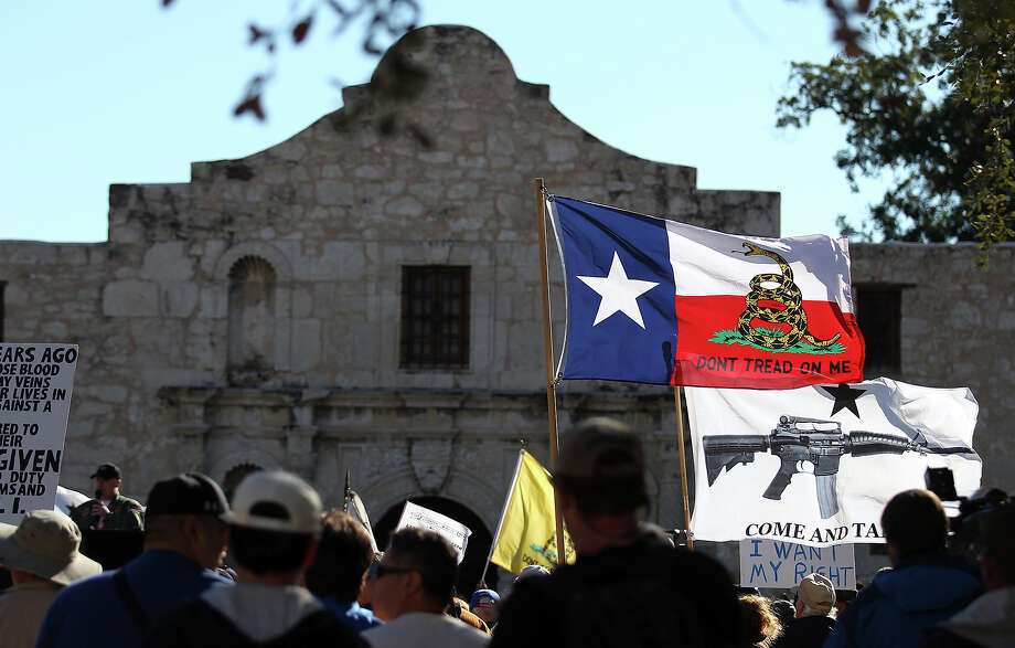 "FILE - In this Oct. 19, 2013 file photo, flags fly at the ""Come And Take It San Antonio"" rally. Long depicted as the rootin'-tootin' capital of American gun culture, Texas is one of the few states with an outright ban on the open carry of handguns. That could change next year, with an expected push for expanding gun rights from the Republican-dominated Legislature. (AP Photo/San Antonio Express-News, Kin Man Hui, File) Photo: Kin Man Hui, MBO / San Antonio Express-News"