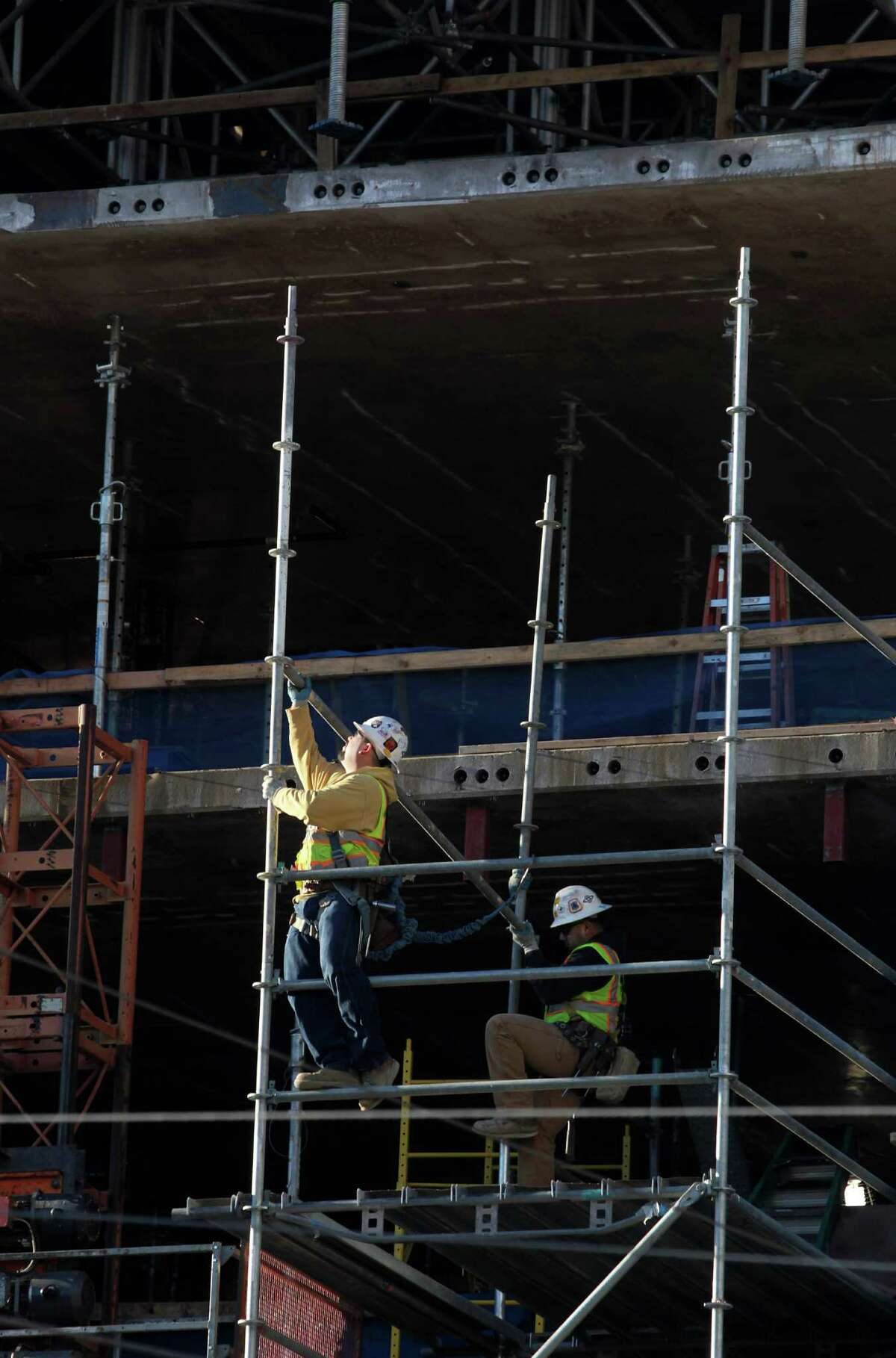 Construction workers build scaffolding for a residential project at 10th and Mission streets in San Francisco on Tuesday.