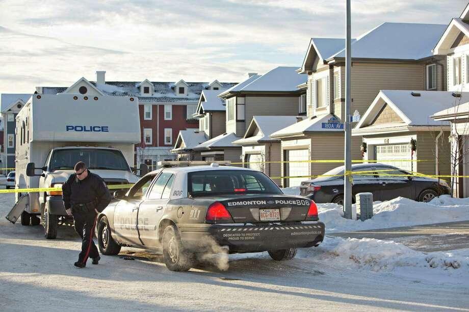 Police investigate the scene where multiple deaths occurred overnight in Edmonton, Alberta, Tuesday, Dec. 30, 2014. (AP Photo/The Canadian Press, Jason Franson) Photo: JASON FRANSON, SUB / The Canadian Press