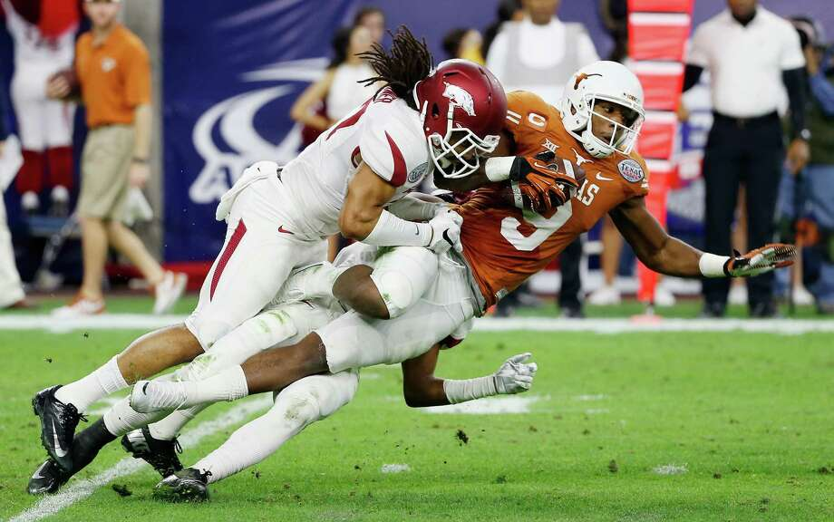Arkansas defensive back Alan Turner tackles UT receiver John Harris during the first half of the Texas Bowl at NRG Stadium in Houston on Dec. 29, 2014. Arkansas won 31-7. Photo: Scott Halleran /Getty Images / 2014 Getty Images