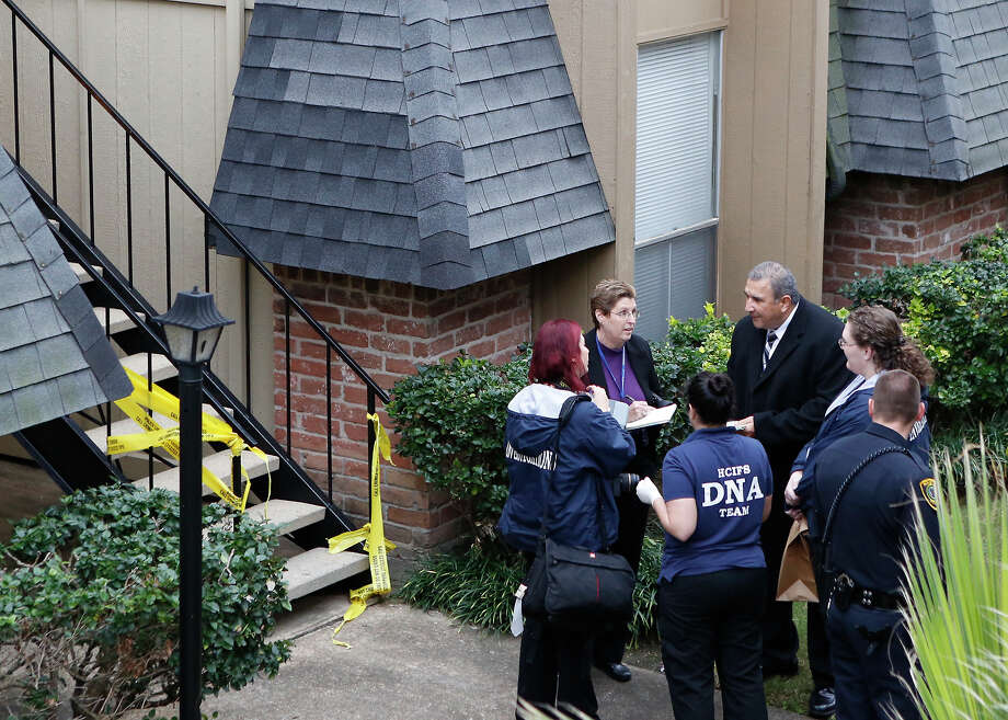Authorities compare notes Tuesday after a woman was found dead at an apartment in the 6900 block of Pinemont. Angel Jackson, 26, was last seen Christmas Eve, and her son was later found safe in Arkansas. Photo: Cody Duty, Staff / © 2014 Houston Chronicle