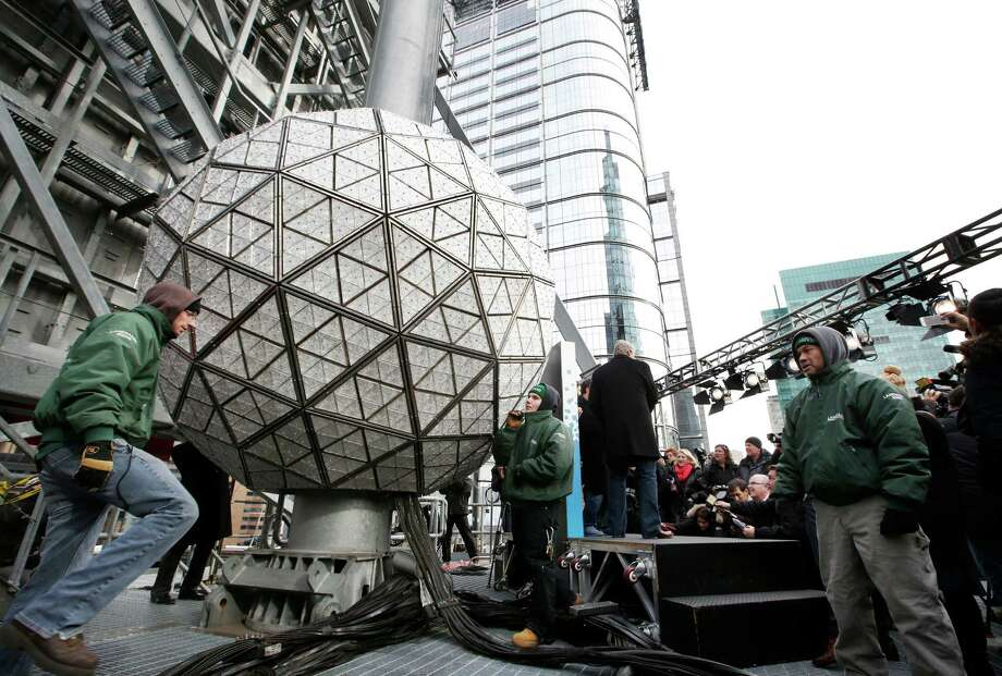 Workers prepare to test the Waterford crystal ball for the New Year's Eve celebration atop One Times Square in New York, Tuesday, Dec. 30, 2014. The ball, which is 12 feet in diameter and weighs 11,875 pounds, is decorated with 2,688 Waterford crystals and illuminated by 32,256 LED lights. Photo: Kathy Willens, Associated Press / AP