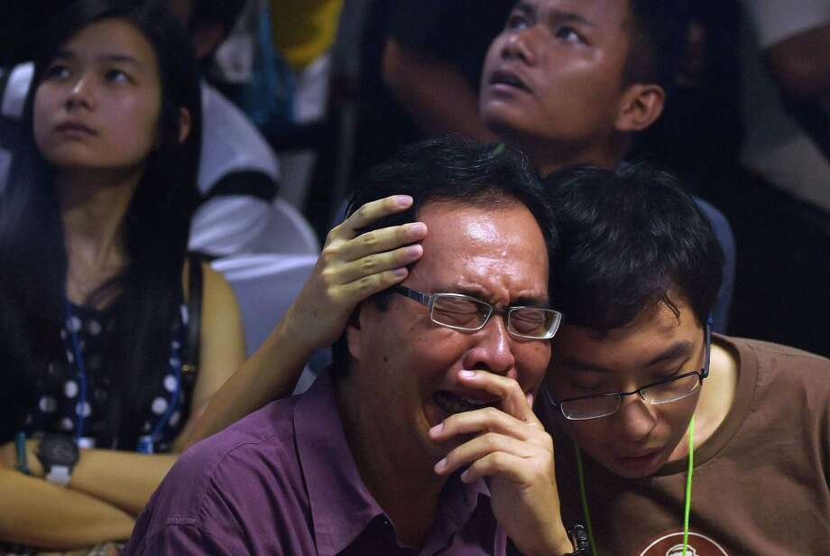 Relatives of AirAsia Flight 8501 passengers watch news reports of an unidentified body found floating in the Java Sea. Debris was found about 60 miles southeast of the plane's last known position. Photo: Manan Vatsyayana /Getty Images / AFP