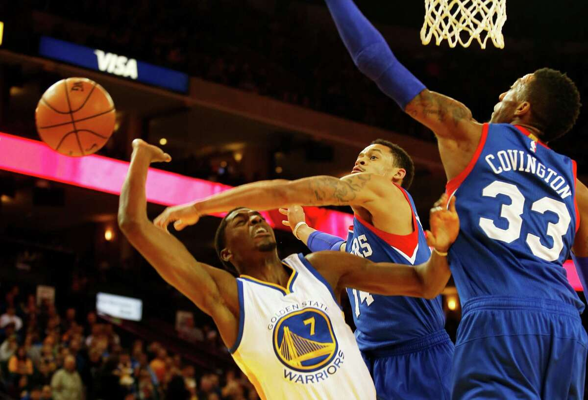 Golden State Warriors guard Justin Holiday, left, is fouled while defended by Philadelphia 76ers guard K.J. McDaniels, center, and forward Robert Covington, right, during the first half of the basketball game on Tuesday, December 30, 2014 in Oakland, Calif.