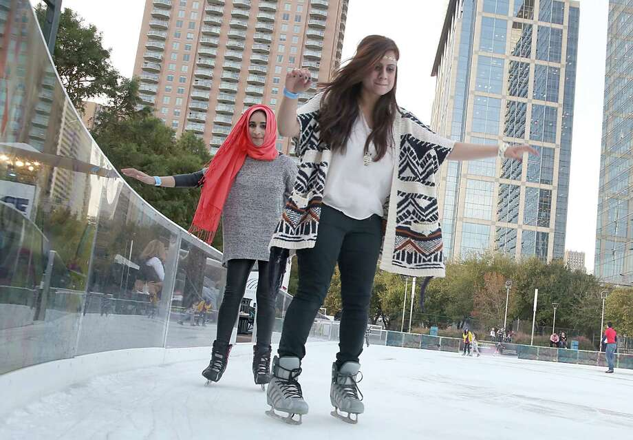 Adults and children skate around Discovery Green Ice Rink on Tuesday, December 9, 2014 in Houston, TX.  A slow camera shutter speed freezes still subjects while bluring those in motion. (Photo: Thomas B. Shea/For the Chronicle) Photo: Thomas B. Shea / Â 2014 Thomas B. Shea