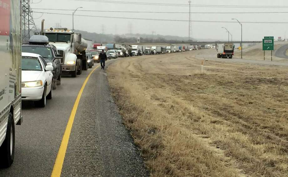Dangerous road conditions including ice have caused a backup along Interstate 10 West north of Kerrville, TX near mile marker 456 on Wednesday, December 31, 2014.  Traffic has been at a standstill for at least an hour or more, with very little traffic flowing East towards San Antonio.  Many passengers have exited their vehicles to head to nearby gas stations while traffic is at a standstill. Photo: Luis Rios, San Antonio Express-News