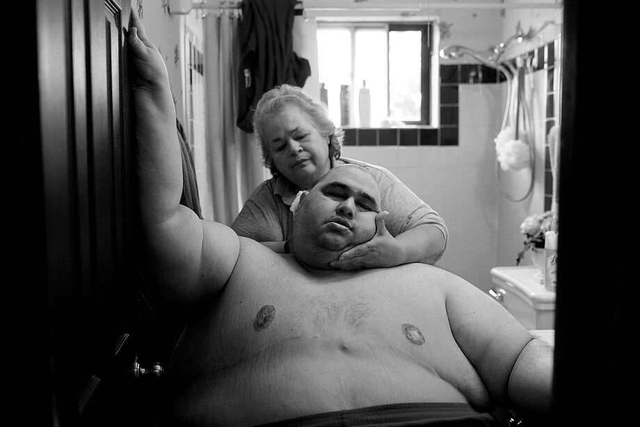 At almost 600 pounds, Hector Garcia Jr. finds simple daily tasks like bathing a challenge. He struggled to walk across the hall from his bedroom to the bathroom so that his mother, Elena, could wash him after having cut his hair in November 2010. A month before, Hector started dieting after he realized he was close to his highest known weight, 636 pounds. Photo: Lisa Krantz, San Antonio Express-News / San Antonio Express-News