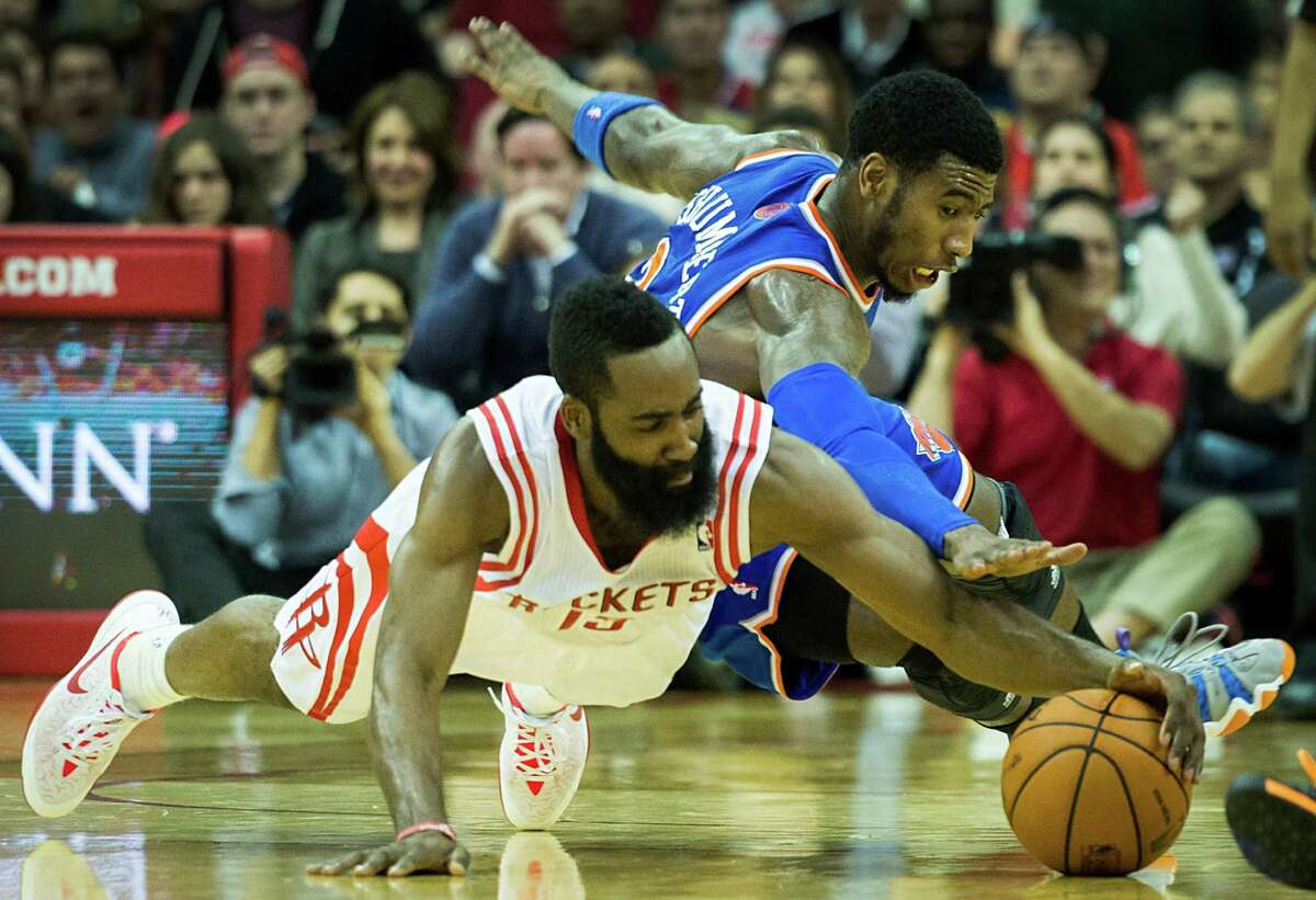 Houston Rockets shooting guard James Harden (13) dives for a loose ball against New York Knicks shooting guard Iman Shumpert (21) during the second half of an NBA basketball game at Toyota Center on Friday, Jan. 3, 2014, in Houston. The Rockets won the game 102-100.