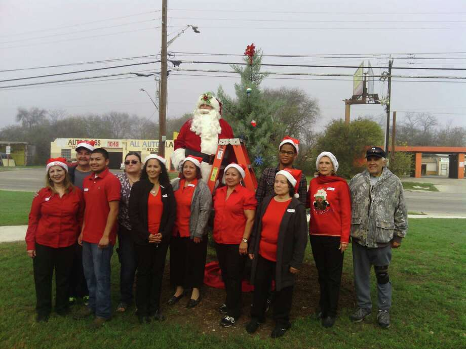 South San residents and friends gather for the neighborhood's first Christmas event. Shown with Santa and the living Christmas tree are, left to right,  Sylvia Lopez, David Lopez ,JJ Olvera ,Tony Cadena ,Pat Limon  Medina ,Francis Narvice  Flores, Angie Lugo Olvera,  Councilman Rey Saldaña's assistant Pat Bruny , Amelia Sanchez , Connie Prado and Raul Prado. Photo: Courtesy / Courtesy