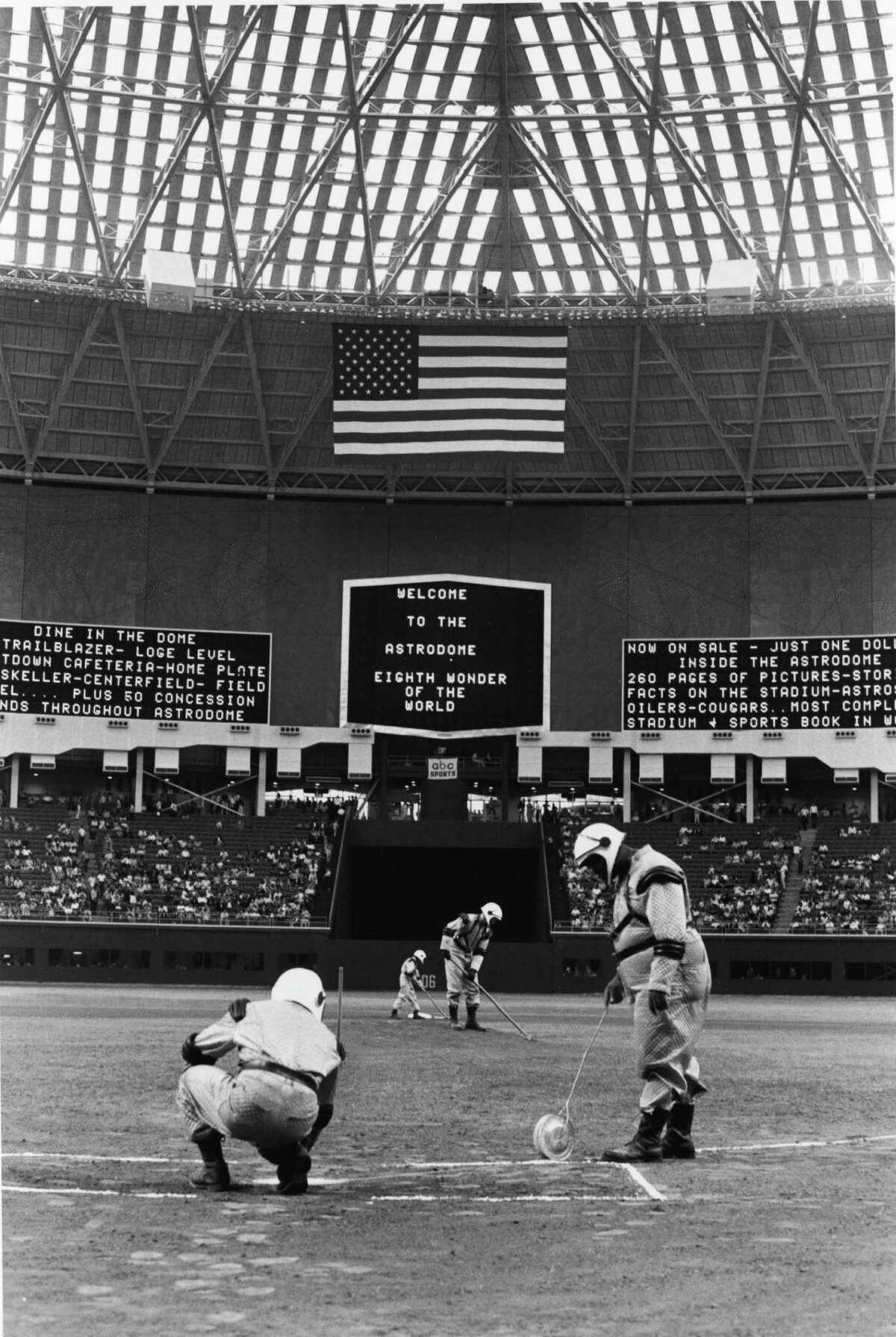 Groundskeepers are forced to wear 'futuristic' spacesuit uniforms as they prepare the diamond for the first game in the Astrodome, Houston, Texas, April 12, 1965. The dome, as seen here, had a translucent roof to allow the grass to grow but glare caused the panes to be painted over, which in turn caused the grass to die. Eventually Monsanto invented AstroTurf, the first and most famous artificial grass replacement.