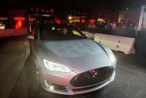 A man test drives Tesla Motors' Model S P85D, which soon will be able to reach 155 mph.