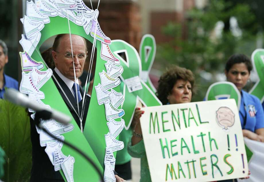 Bexar County Judge Nelson Wolff, circled by an oversided green ribbon with messages by children, parents, and mental illness advocates, listens to a speaker in front of the Bexar County Courthouse in recognition of National Children's Mental Health Awareness Day in 2014. Photo: BOB OWEN, Staff / © 2012 San Antonio Express-News