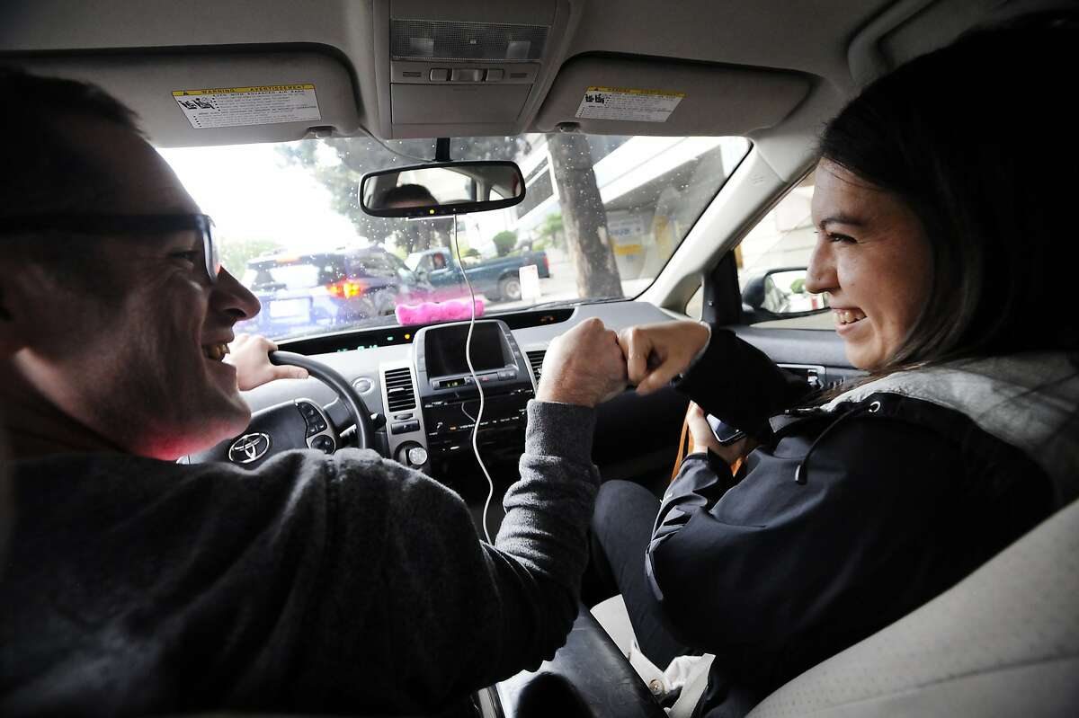 Lyft driver Andrew Kucharski, left, who is deaf, gives a fist bump to customer Esther Fensel upon arriving at her destination, in San Francisco, CA, on Wednesday, December 17, 2014. To communicate Andrew uses a keyboard that both he and his passengers can type on which is also synced with his iPhone where the messages are displayed.