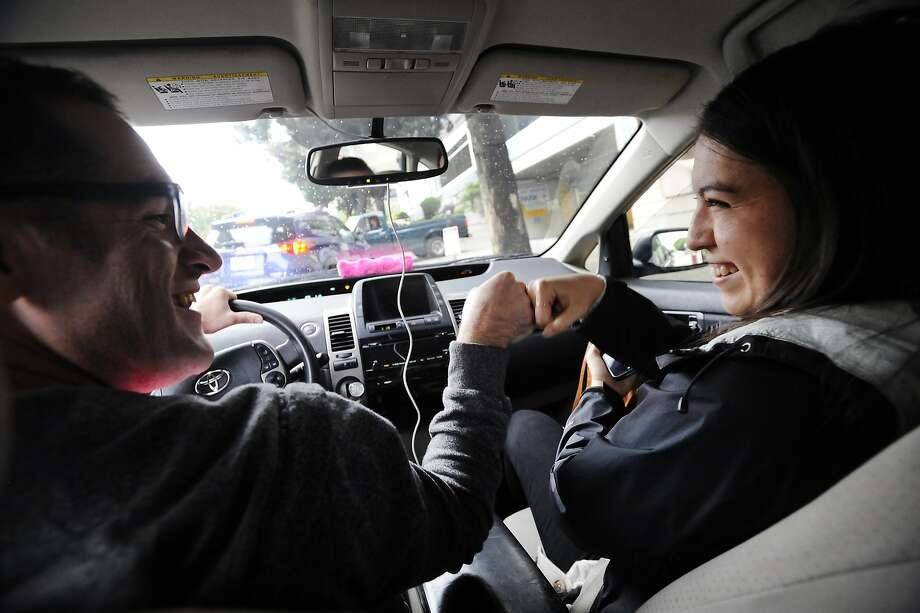 Lyft driver Andrew Kucharski, left, who is deaf, gives a fist bump to customer Esther Fensel upon arriving at her destination, in San Francisco, CA, on Wednesday, December 17, 2014.  To communicate Andrew uses a keyboard that both he and his passengers can type on which is also synced with his iPhone where the messages are displayed. Photo: Michael Short, Special To The Chronicle