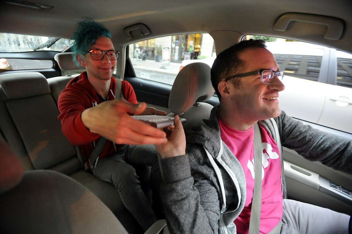 Lyft driver Andrew Kucharski, right, who is deaf, hands his keyboard to passenger Jeremy Mikush from Los Angeles, so he can communicate with Andrew, in San Francisco, CA, on Wednesday, December 17, 2014. To communicate Andrew uses a keyboard that both he and his passengers can type on which is also synced with his iPhone where the messages are displayed.