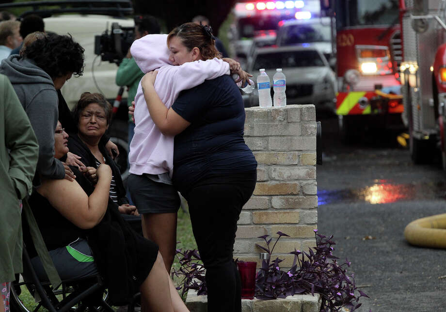 Freinds and family of the dweller of a home on the 8700 block of Bridington embrace Monday November 3, 2014 after the home in the Brookwood subdivision burned. Several area volunteer fire departments responded to the blaze which is being investigated. Photo: JOHN DAVENPORT, San Antonio Express-News / ©San Antonio Express-News/John Davenport