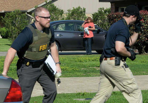 The FBI, Friday morning, searched the homes of Naomi Lawrence Lee BISD's purchasing director and William 'Bo' Kelley the former West Brook Booster Club president. A neighbor is seen watching FBI agents walking toward Kelley's home. Photo taken Friday, April 04, 2014 Guiseppe Barranco/@spotnewsshooter Photo: Guiseppe Barranco, Photo Editor