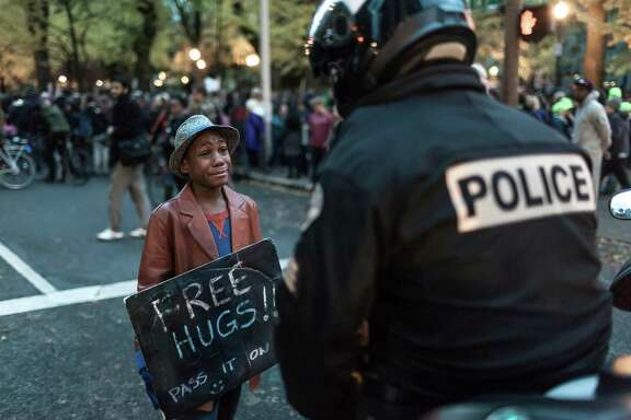 Devonte Hart and Portland, Oregon police officer Bret Barnum have their special moment.  Protest in front of the Justice Center to protest the Mike Brown, Ferguson verdict.  ©jan sonnenmair 2014.
