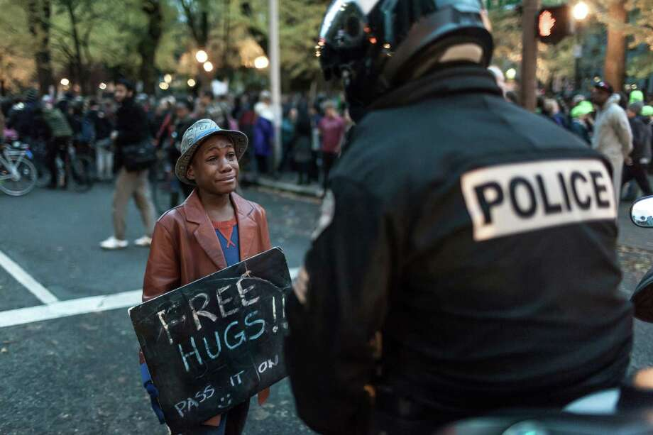 Devonte Hart and Portland, Oregon police officer Bret Barnum have their special moment.  Protest in front of the Justice Center to protest the Mike Brown, Ferguson verdict.  © Jan Sonnenmair 2014 Photo: Jan Sonnenmair / Special To The Chronicle / ONLINE_CHECK