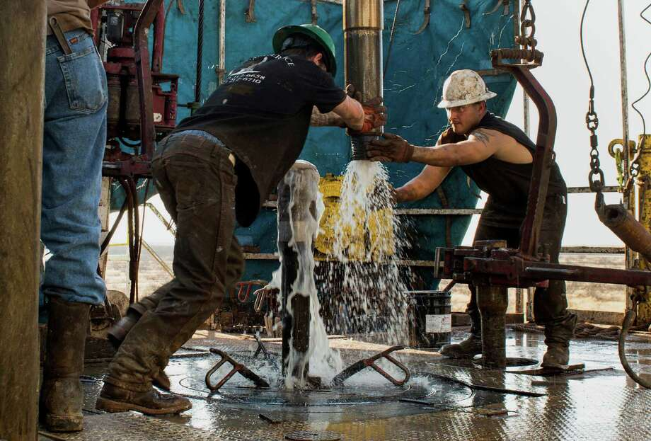 Workers connect drill bits and drill collars, used to extract natural petroleum, in the Permian Basin. The oil industry laid off about 150,000 workers around the world in the past year, energy recruiting firm Swift Worldwide Resources estimates, and producers around the world are likely to cut more positions as they delay deep-water oil projects and ax capital investments as long as oil prices are rocking up and down, said Tobias Read, CEO of Swift. Photo: Bloomberg News File Photo / © 2014 Bloomberg Finance LP