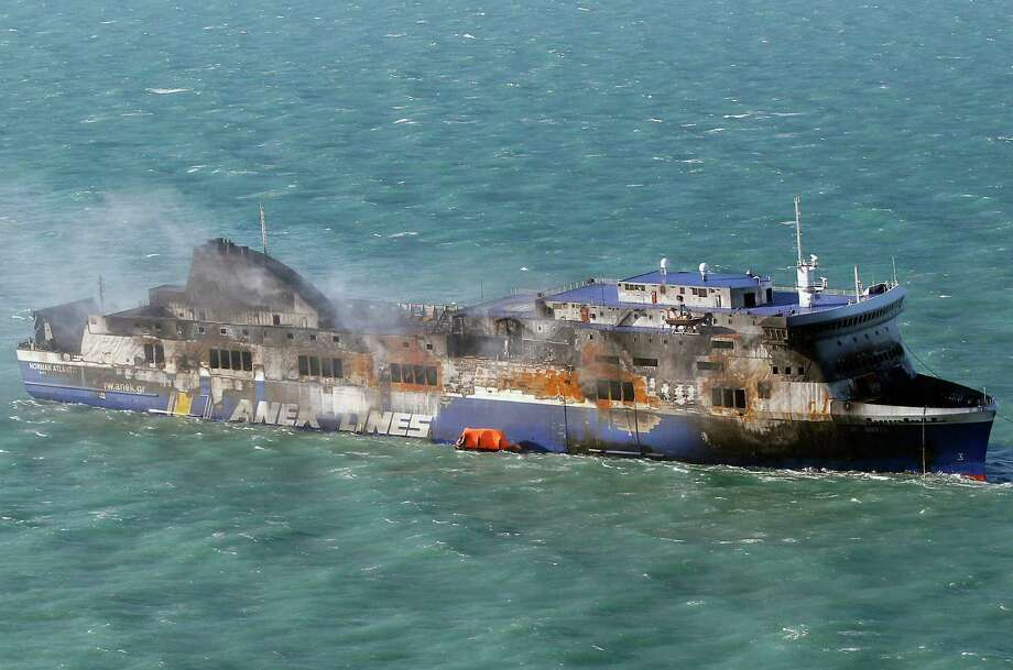 """Smoke billows from the Italian-flagged Norman Atlantic ferry that caught fire in the Adriatic Sea, Tuesday, Dec. 30, 2014. A blaze broke out on the car deck of the Norman Atlantic Sunday, Dec. 28, while the ferry was traveling from the Greek port of Patras to Ancona in Italy causing the death of at least 11 people. Italian and Greek helicopter rescue crews evacuated 427 people among passengers and crew members but Italian officials think the death toll could be much higher because of serious discrepancies in the ship's manifest and confusion over how many people were aboard. """"We cannot say how many people may be missing,"""" Italian Transport Minister Maurizio Lupi said at a news conference. The cause of the fire is under investigation. (AP Photo/Antonio Calanni) Photo: Antonio Calanni, STF / AP"""