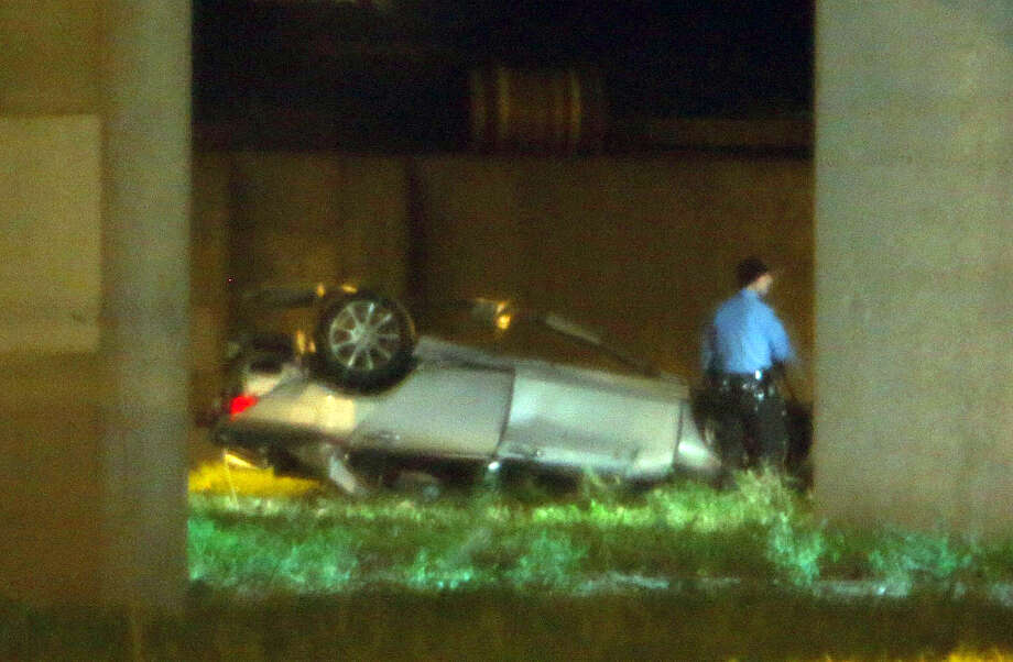 A car fell off the overpass along U.S. 59 after crashing into an HPD car on New Year's Eve. Photo: James Nielsen, Chronicle