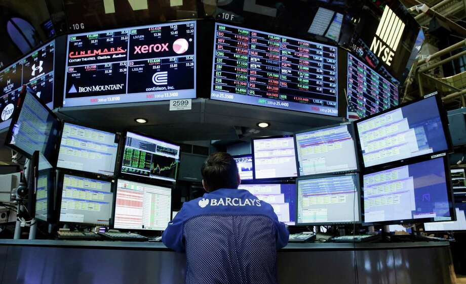 Specialist Charles Solomon works at his post on the floor of the New York Stock Exchange earlier this year. Utilities stocks rose the most in the S&P 500 in 2014, while the energy sector lagged as the price of oil collapsed. Photo: Richard Drew /Associated Press / AP