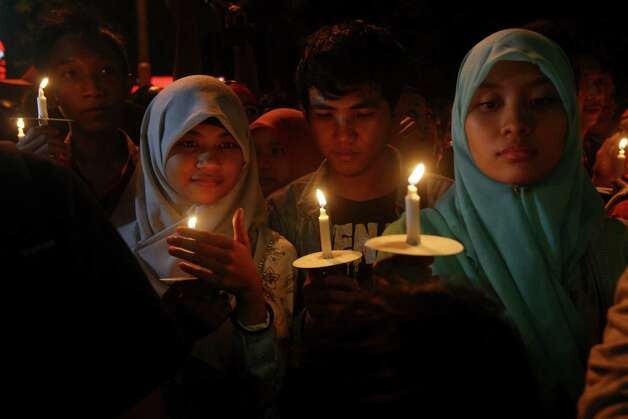 Indonesian hold candles to pray for the victims of AirAsia Flight 8501 in Surabaya, Indonesia, Wednesday, Dec. 31, 2014. Bad weather hindered efforts to recover victims of the jet on Wednesday, and sent wreckage drifting far from the crash site, as grieving relatives prayed for strength to endure their losses. (AP Photo/Firdia Lisnawati) ORG XMIT: XFL119 Photo: Firdia Lisnawati / AP