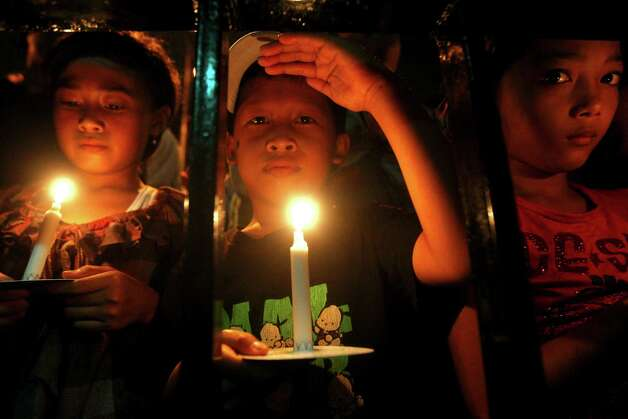 Indonesian children hold candles to pray for the victims of AirAsia Flight 8501 in Surabaya, Indonesia, Wednesday, Dec. 31, 2014. Bad weather hindered efforts to recover victims of the jet on Wednesday, and sent wreckage drifting far from the crash site, as grieving relatives prayed for strength to endure their losses. (AP Photo/Firdia Lisnawati) ORG XMIT: XFL117 Photo: Firdia Lisnawati / AP
