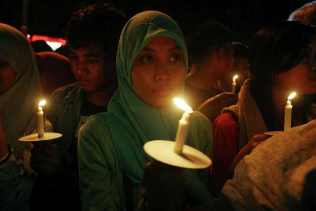 Indonesians hold candles to pray for the victims of AirAsia Flight 8501 in Surabaya, Indonesia, Wednesday, Dec. 31, 2014. Bad weather hindered efforts to recover victims of the jetliner on Wednesday, and sent wreckage drifting far from the crash site, as grieving relatives prayed for strength to endure their losses. (AP Photo/Firdia Lisnawati) ORG XMIT: XFL115 Photo: Firdia Lisnawati / AP