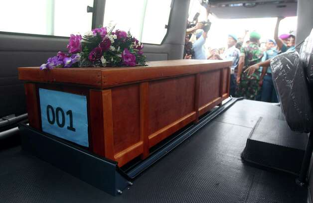 """A coffin of a victim of AirAsia Flight 8501 is placed inside a vehicle upon arrival at Indonesian Military Air Force airport in Surabaya, Indonesia, Wednesday, Dec. 31, 2014. Bad weather hindered efforts to recover victims of the jetliner Wednesday, and sent wreckage drifting far from the crash site, as grieving relatives """"surrounded in darkness"""" gathered in an airport and prayed for the strength to move forward. (AP Photo/Firdia Lisnawati) ORG XMIT: XFL113 Photo: Firdia Lisnawati / AP"""