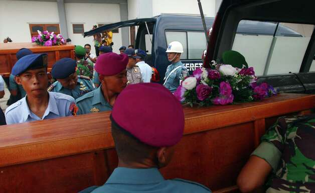 """Indonesian soldiers carry coffins of victims of AirAsia Flight 8501 upon arrival at  Indonesian Military Air Force airport in Surabaya, Indonesia, Wednesday, Dec. 31, 2014. Bad weather hindered efforts to recover victims of the jetliner Wednesday, and sent wreckage drifting far from the crash site, as grieving relatives """"surrounded in darkness"""" gathered in an airport and prayed for the strength to move forward. (AP Photo/Firdia Lisnawati) ORG XMIT: XFL110 Photo: Firdia Lisnawati / AP"""