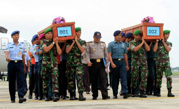 """Indonesian soldiers carry the bodies of victims of AirAsia Flight 8501 upon arrival at  Indonesian Military Air Force airport in Surabaya, Indonesia, Wednesday, Dec. 31, 2014. Bad weather hindered efforts to recover victims of the jetliner Wednesday, and sent wreckage drifting far from the crash site, as grieving relatives """"surrounded in darkness"""" gathered in an airport and prayed for the strength to move forward. (AP Photo/Firdia Lisnawati) ORG XMIT: XFL108 Photo: Firdia Lisnawati / AP"""
