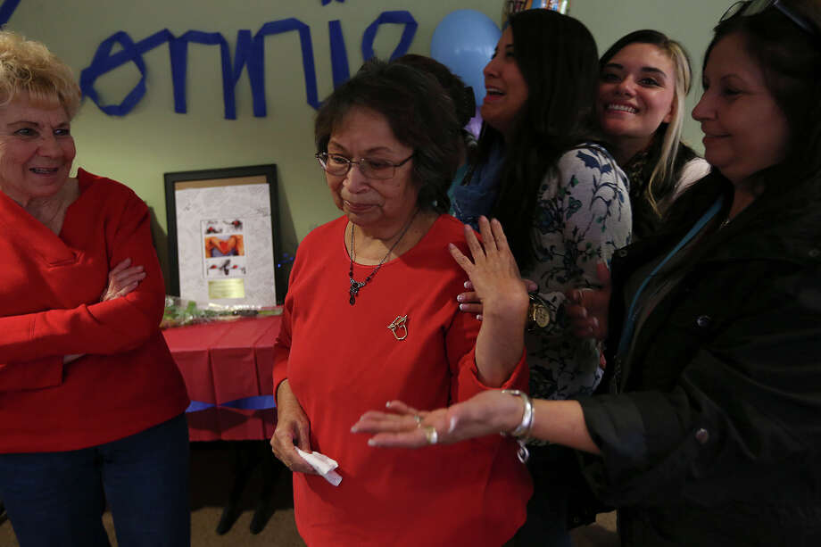 Surrounded by co-workers, Connie Acuna, center racts during her surprise retirement party at the Children's Shelter, Tuesday, Dec. 30, 2014. Acuna is retiring after 37 years at the shelter. Photo: JERRY LARA, Staff / San Antonio Express-News / © 2014 San Antonio Express-News