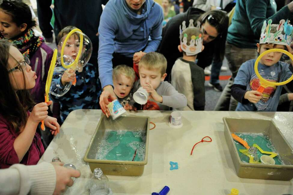 Children blow bubbles during a New Year's celebration at the CNSE Children's Museum of Science and Technology on Wednesday, Dec. 31, 2014, in North Greenbush, N.Y. The children and adults rang in the new year at 12 noon during the event at the museum. (Paul Buckowski / Times Union)