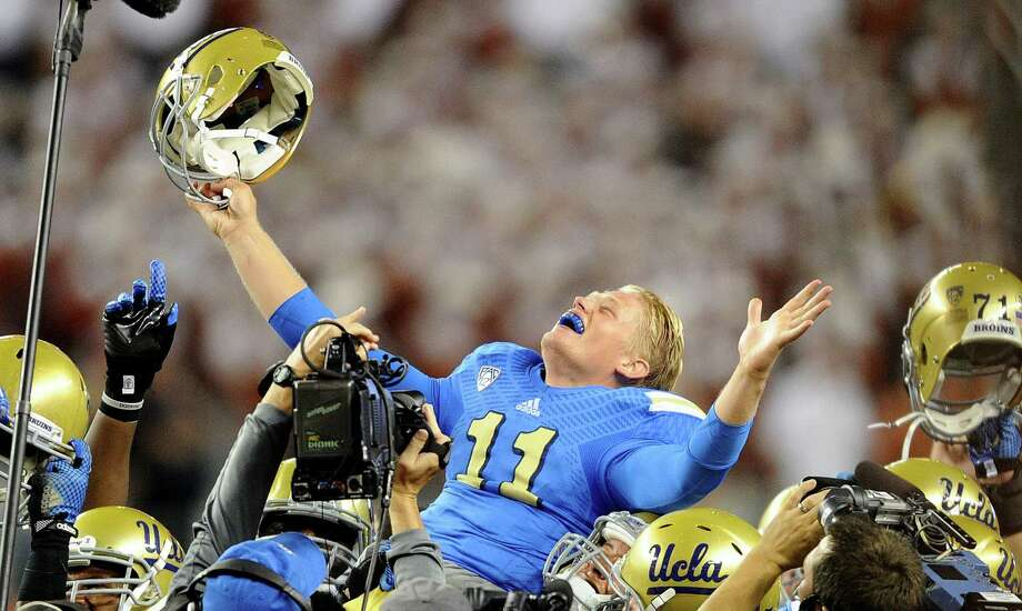 UCLA quarterback Jerry Neuheisel is lifted into the air by teammates after defeating Texas, 20-17, at AT&T Stadium in Arlington on Sept. 13, 2014. Photo: Wally Skalij /McClatchy-Tribune News Service / Los Angeles Times