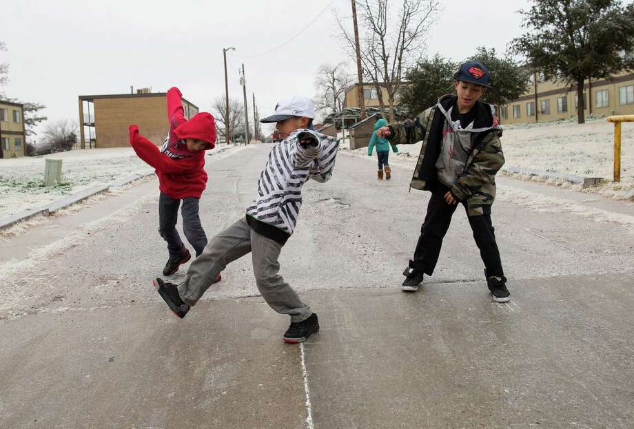 Chris Glosson, left, Isaiah Carrillo, center, and his brother, Angel, slide down an icy alley in Odessa. Much of West Texas was dealing with ice and snow. Winter warnings also were issued for other parts of the state. Photo: Courtney Sacco, MBR / Odessa American