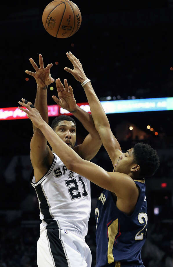 Tim Duncan passes from the high post against Anthony Davis as the Spurs play the Pelicans at the AT&T Center on Dec. 31, 2014. Photo: Tom Reel /San Antonio Express-News