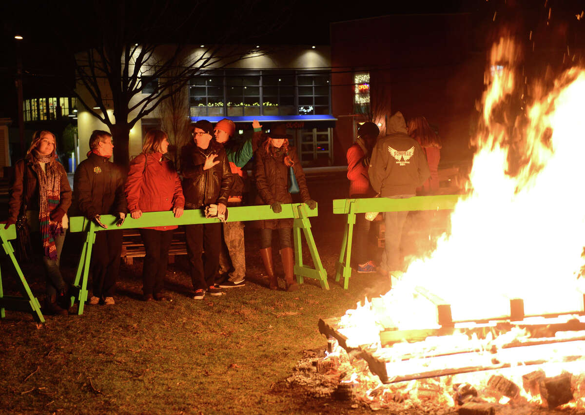 Revelers take a moment between activities to get warm by a fire set up on Jesup Green, during the First Night New Year's Eve celebration for Westport and Weston in downtown Westport, Conn. on Thursday Dec. 31, 2014.