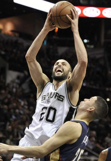 San Antonio Spurs guard Manu Ginobili, left, of Argentina, shoots against New Orleans Pelicans guard Austin Rivers in the second half of an NBA basketball game, Wednesday, Dec. 31, 2014, in San Antonio. San Antonio won 95-93 in overtime. (AP Photo/Darren Abate) Photo: Associated Press