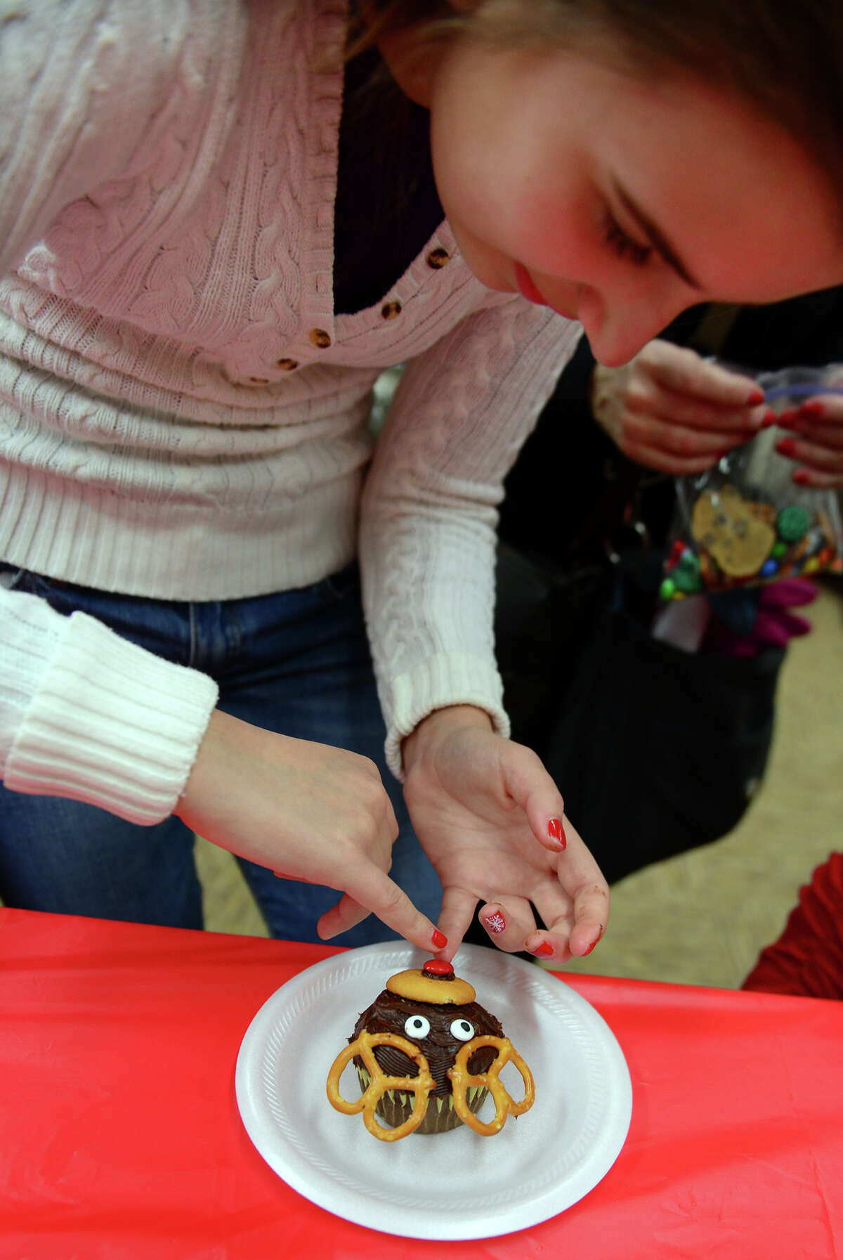 Gabriella Rodia, 12, of Trumbull, puts the finishing touch, a red M&M, on a cupcake she decorated at a First Night Cupcake Party held at the Westport Library, during the First Night New Year's Eve celebration for Westport and Weston in downtown Westport, Conn. on Thursday Dec. 31, 2014.