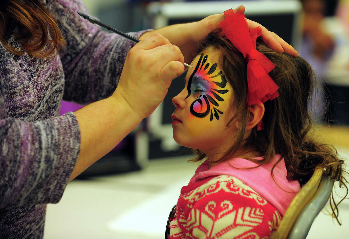 Liliana Veloso, 3, of Westport, gets her face painted by Betty Lopes, with Amazing Face Art out of West Hartford, at Saugatuck Elementary School during the First Night New Year's Eve celebration for Westport and Weston in downtown Westport, Conn. on Thursday Dec. 31, 2014.
