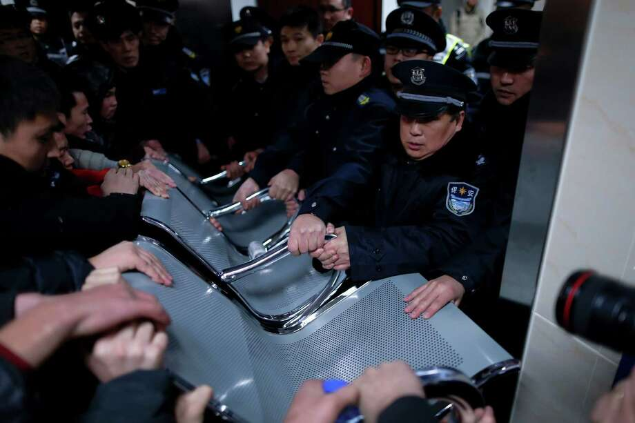Security guards use a bench to hold off relatives of stampede victims trying to enter the emergency area of a hospital in Shanghai, China, Thursday, Jan. 1, 2015. Dozens died in a stampede during New Year's celebrations in downtown Shanghai, city officials said - the worst disaster to hit one of China's showcase cities in recent years. (AP Photo) CHINA OUT Photo: STR / CHINATOPIX