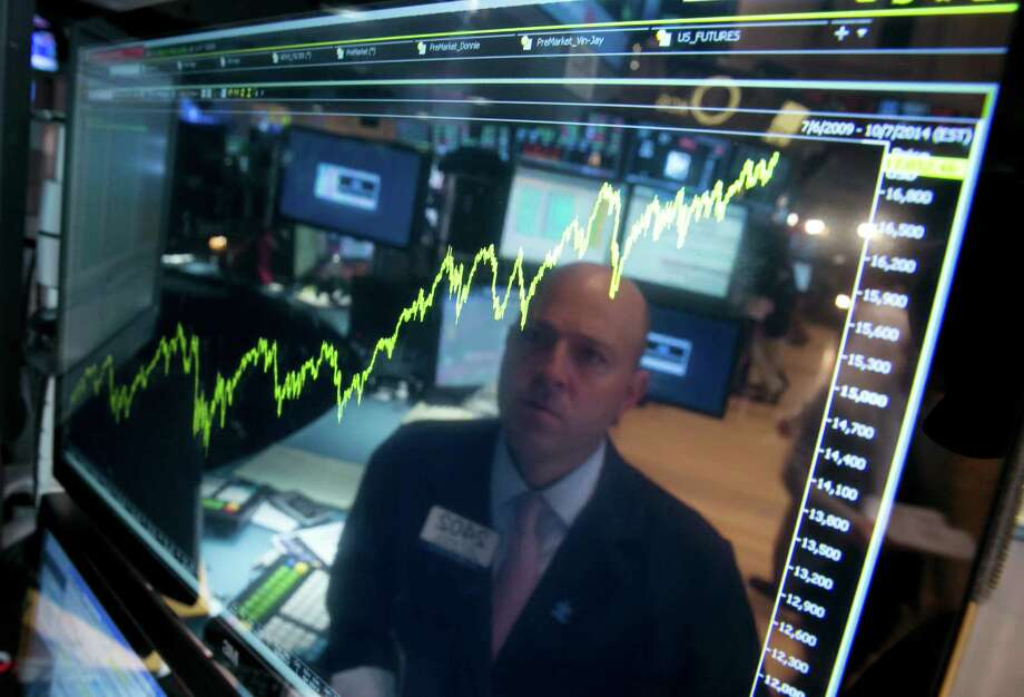 Stock specialist Jay Woods takes time in July to look at five years of the Dow Jones industrial average. Photo: Richard Drew, STF / AP