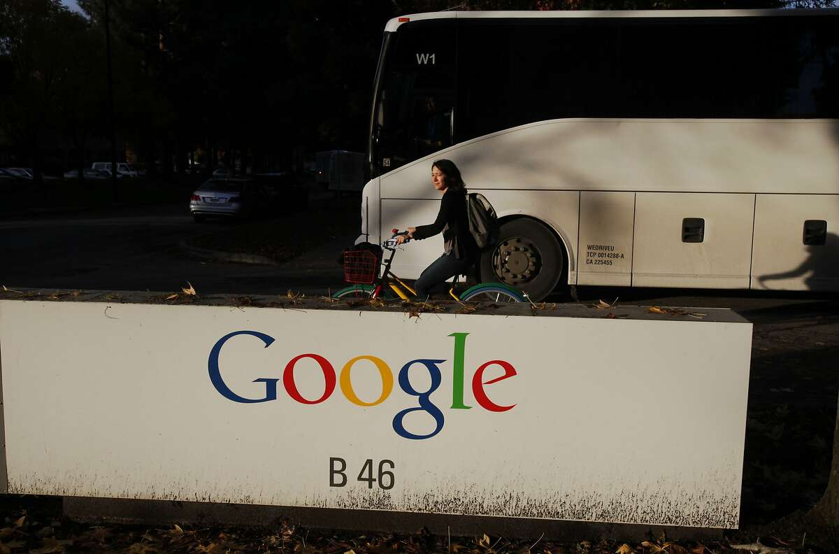 An employee rides a Google bike as a Google bus drives past the Google sign at Google's Mountain View headquarters Dec. 4, 2014 in Mountain View, Calif.