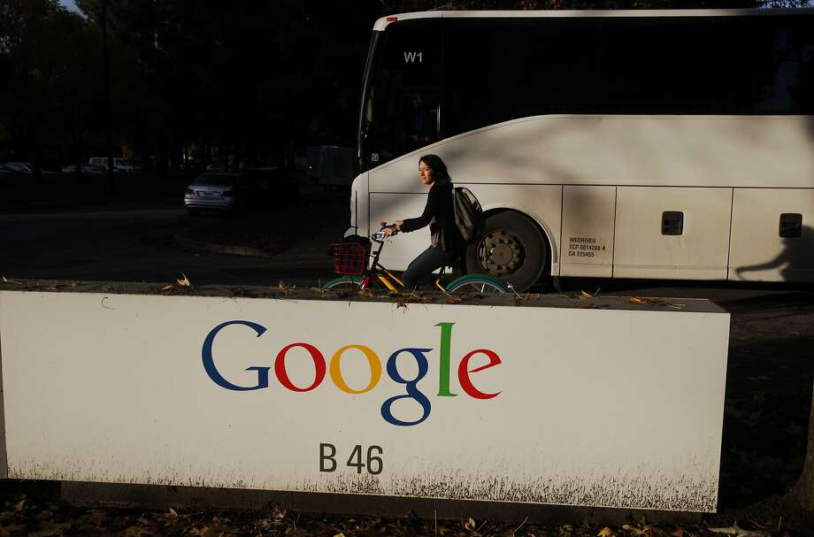 An employee rides a Google bike as a Google bus drives past the Google sign at Google's Mountain View headquarters Dec. 4, 2014 in Mountain View, Calif. Photo: Leah Millis, The Chronicle