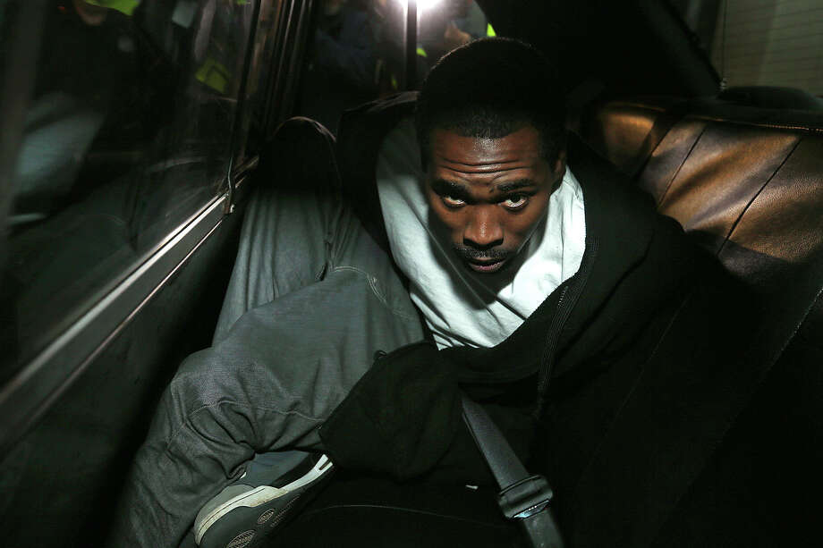 Olice Brown, 28, sits in a patrol car after he was escorted out of the San Antonio Police Headquarters, Wednesday, Dec. 31, 2014. Brown is facing capital murder charges in the deaths of Cornell Glover, Sr., 38 and his son, Cornell Glover, Jr., 19. Photo: JERRY LARA /San Antonio Express-News / © 2014 San Antonio Express-News